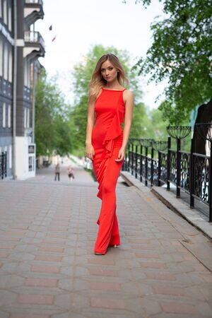 A beautiful blonde in an elegant red dress and high heels is walking along a deserted city street