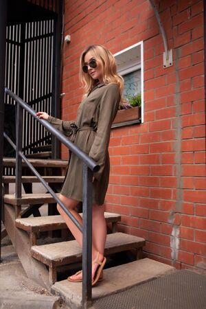 A charming blonde girl in stylish black glasses is standing on the stairs. Fashion photography. Zdjęcie Seryjne