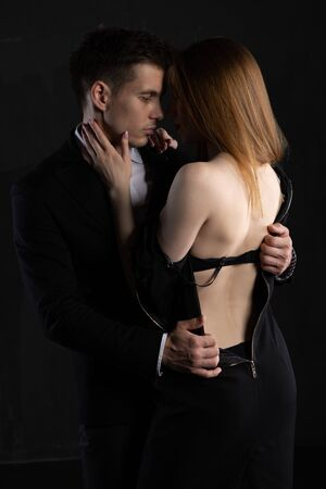 Concept photo of a sexy elegant couple in a tender passion. A man undresses his girlfriend during a hug