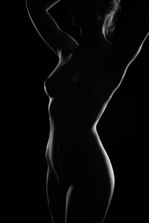 Nude art, perfect Nude body of a sexy young woman on a dark background, black and white shot Studio shot. A beautiful naked female body in a contoured light