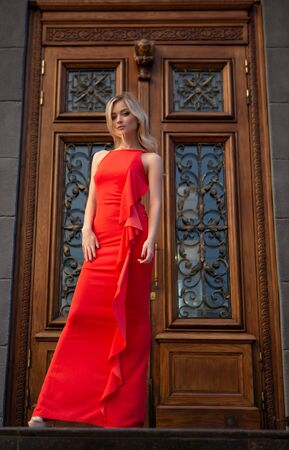 Sexy blonde with big blue eyes in a red evening dress poses gracefully on a city street Zdjęcie Seryjne