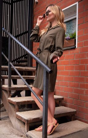 a beautiful blue eyed blonde girl adjusts her sunglasses while standing on a metal staircase