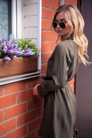An elegant blue-eyed blonde girl in dark glasses stands on the street at the window with flowers. Fashion portrait