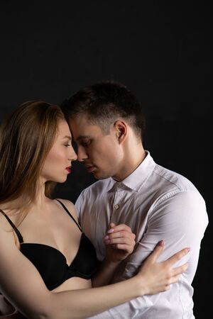 a girl in black underwear gently embraces her cute man in a white shirt. Tender relationship of a loving couple