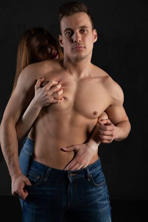 A sexy, muscular, naked man and a womans hands are unbuttoning his jeans. A woman standing behind caresses a man with a naked torso Фото со стока