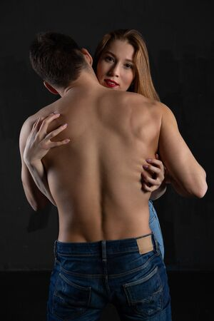 Sexy blonde girl embraces a muscular man with a naked torso in jeans