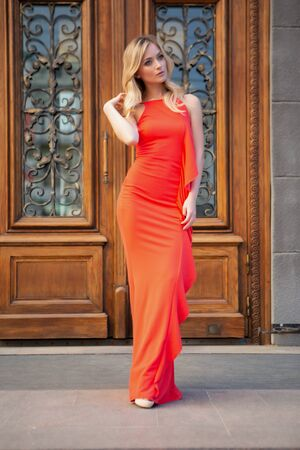 A beautiful sexy blonde girl with big blue eyes in a red dress poses gracefully on a city street