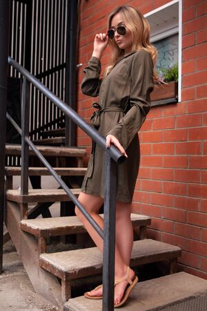 a pretty blonde girl in a green dress and dark glasses stands on a street staircase in summer. A well-dressed European woman spends time in the city. Fashion photography Zdjęcie Seryjne