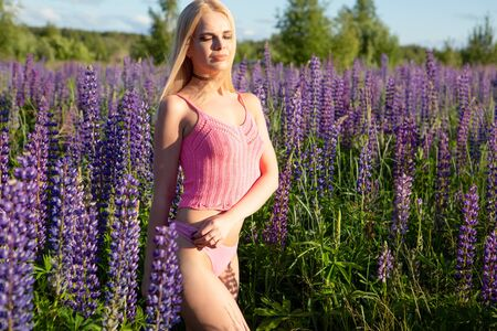 A gorgeous blonde girl with a beautiful body in underwear stands with her eyes closed on a blooming field lit by bright sunlight Banque d'images