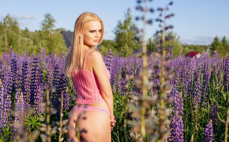 A gorgeous blonde girl in underwear with a beautiful booty stands on a blooming field in a sexy pose. Slender girl with a beautiful body Banque d'images