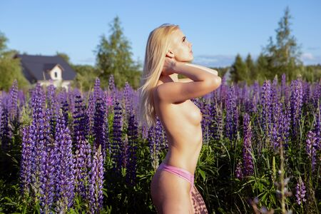 a young blonde girl with a beautiful neat chest adjusts her hair flowing in the wind standing on a blooming field Topless Banque d'images - 147969313