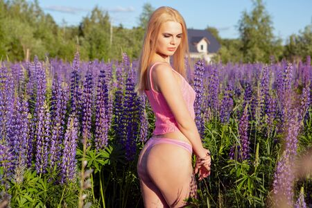 a gorgeous blonde girl in pink underwear stands on a blooming field looking down romantically Banque d'images