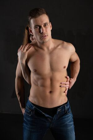 A sexy, muscular, naked man and a womans hands are unbuttoning his jeans. Passion between a man and a woman Banque d'images