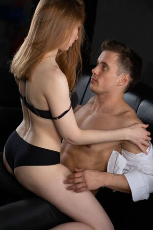 a manly beefy handsome man embraces a sexy woman in black underwear sitting on top of him, they are sitting on a leather sofa in the bedroom Banque d'images