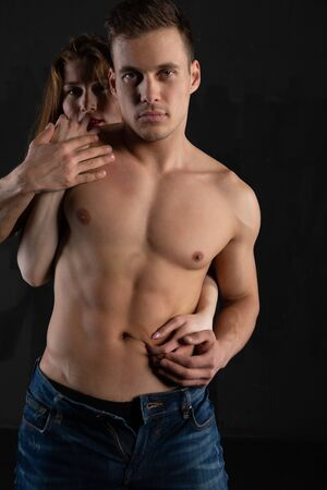 a blonde girl standing behind a sexy pumped-up man passionately strokes his athletic body. Studio portrait