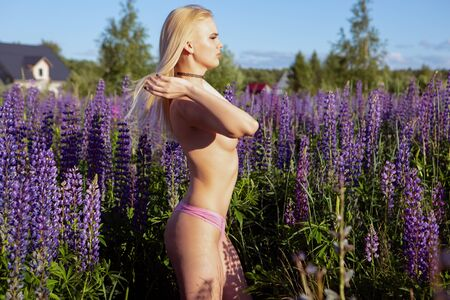 a young blonde girl with a beautiful neat chest adjusts her hair flowing in the wind standing on a blooming field Topless