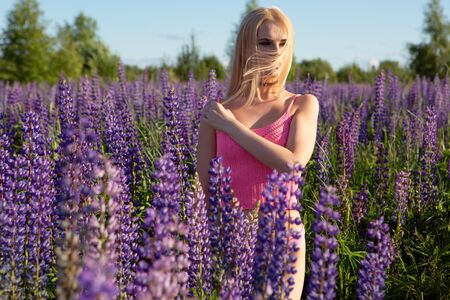 A gorgeous blonde girl with a beautiful body in underwear stands on a blooming field lit by bright sunlight with her hair flowing in the wind. Girl in nature.