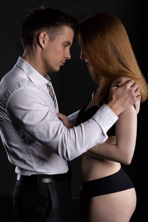 A sexy blonde girl in black underwear slowly unbuttons the shirt of a man who is gently embracing her Banque d'images