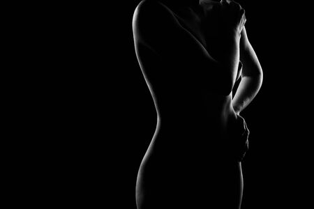 A silhouette of a naked woman with a magnificent figure covering her beautiful Breasts with her hands. Close-up portrait on a dark background
