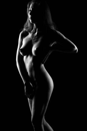 beautiful Nude female body on a black background. Black and white photo of a beautiful Nude female body