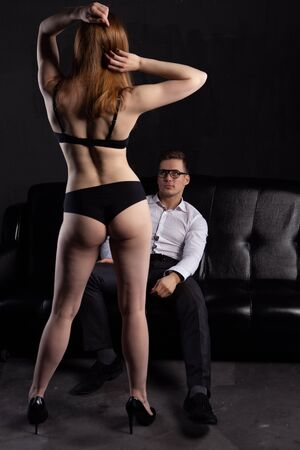 A young man sits on a sofa and looks at an attractive woman in underwear who seduces him Banque d'images