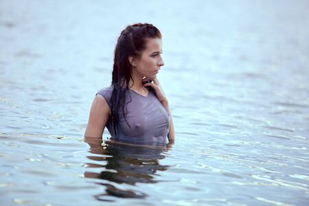 a charming brunette girl stands in the river dressed in a wet t-shirt through which sexy Breasts are visible. Wet t-shirt. Woman bathing