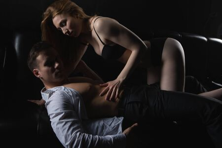 beautiful sexy blonde woman in black lingerie undresses a man during foreplay in the bedroom. Lovers in tender passion