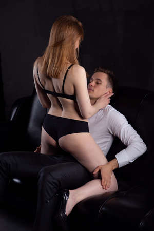 Sexy young couple. Undressed sensual blonde woman with a beautiful body in black underwear sits on a muscular man, kissing undressing him in the room on a dark background. Studio vertical photography
