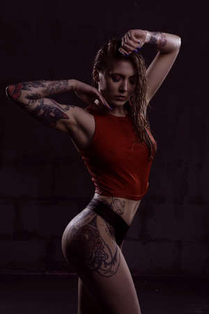 Portrait of a beautiful young sexy woman in a red wet t-shirt on a black background. Studio photography
