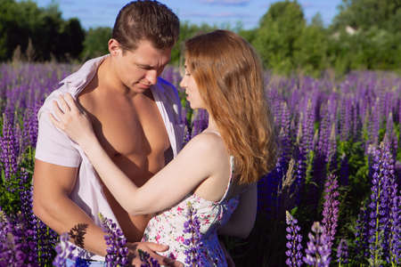 An emotional scene, a young red-haired woman undressing her partner in a blooming bright field on a Sunny day