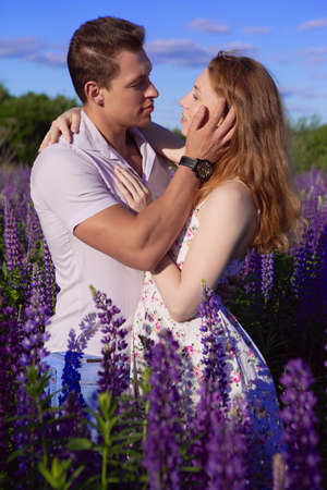 A young couple in love tenderly embraces on a field of beautiful and bright lupins
