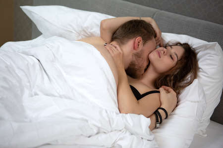 young loving couple lying in each other's arms and kissing in bed at home