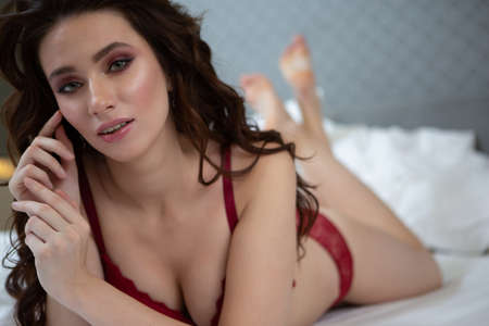 Charming girl in red lace lingerie with sexy look looks at the camera