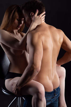 Passionate embrace of a sexy couple in love during foreplay in a dark room
