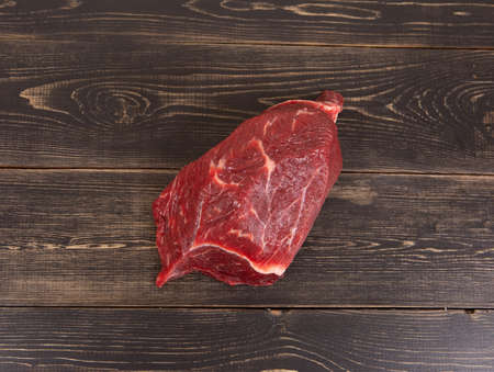 Fresh raw beef meat before cooking on a brown wooden background Banque d'images