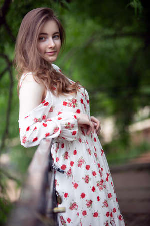 A gorgeous woman in a light summer dress leaned against a bridge over a small river in a city Park on a warm Sunny day. Close-up portrait