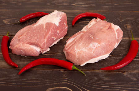 Raw juicy and fresh meat steaks with red pepper, ready for frying on a wooden background.