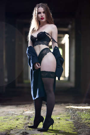 Sexy brunette in black underwear and stockings in an old abandoned building in a contoured light