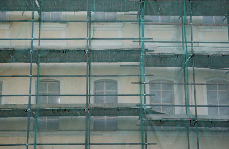 The old building is under restoration. The scaffolding is installed and protected by a strong green mesh for safety