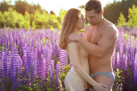 A young Nude couple lovingly embraces on a blooming field during a beautiful sunset