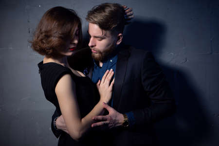 a young couple passionately embraces in a room with low lighting. Close-up portrait.