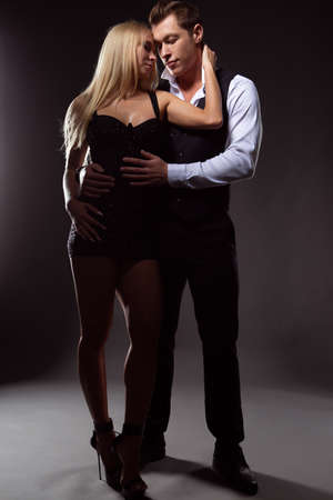 elegant young couple in love tenderly embracing on a dark background