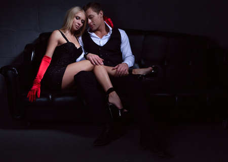 Young glamorous passionate couple sitting on the couch in the semi-darkness