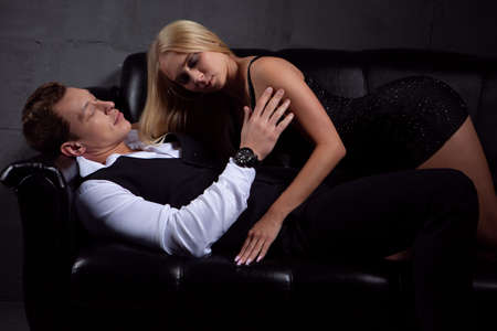 A sexy woman in a black dress kisses a beautiful man lying on the sofa. Close-up photo