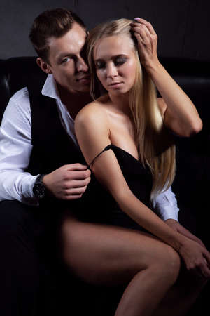 A man removes a dress from his favorite sexy woman sitting on a black sofa, close-up photo