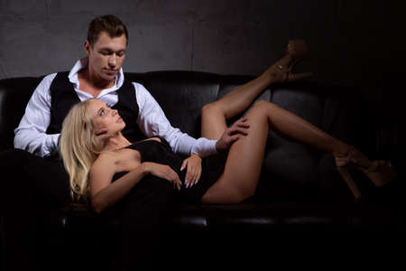 A young charming blonde woman is lying on the lap of her beloved man sitting on a black leather sofa in a dimly lit room
