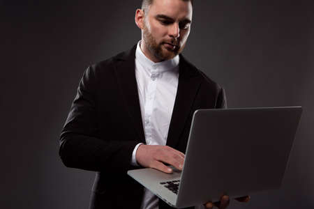 An image of a focused, brutal businessman working on a laptop that he holds in his hand. Close-up photo on a dark background