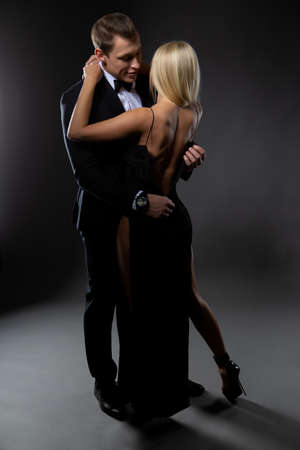 A handsome man unbuttons the dress of his favorite sexy blonde woman during a tender embrace. Photo on a dark background Banque d'images