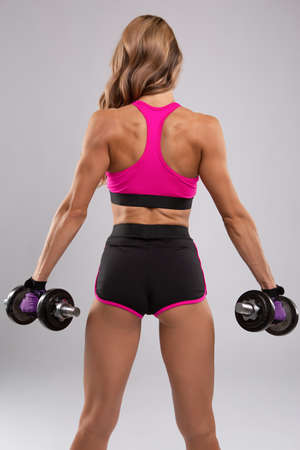 A good woman with a beautiful athletic body does a workout with dumbbells isolated on a white background