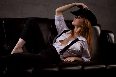 gorgeous woman in an unbuttoned shirt dressed on a body sitting in a pose on a black leather sofa